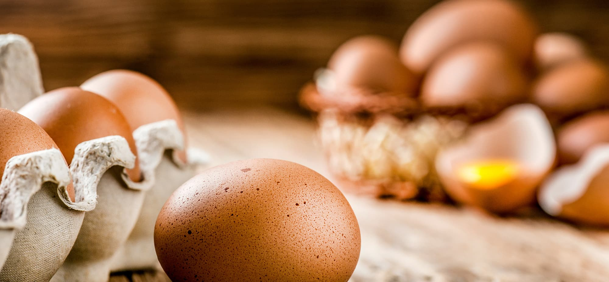 Image of a carton of eggs on a wooden board