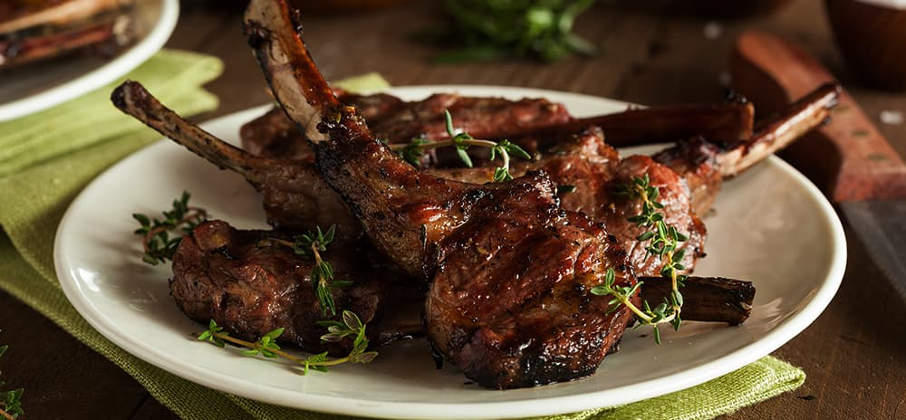 Image is of cooked lamb cutlets on a plate